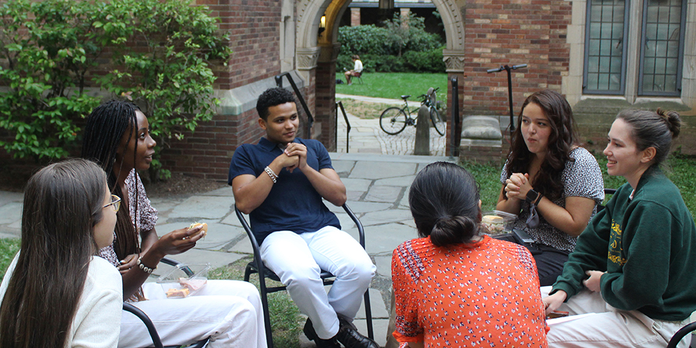 A group of students in conversation, seated in the courtyard