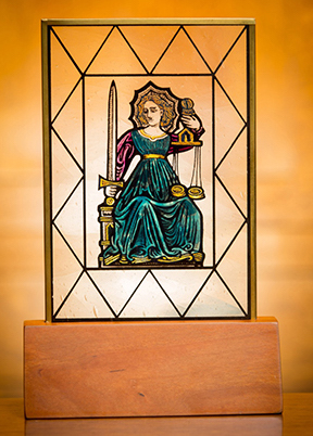 stained glass medallion resting in an oak base with a brass plaque